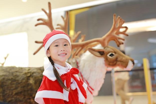 Glückliches kleines kindermädchen in sankt-kostüm auf winterzeit. frohe weihnachten und ein glückliches neues jahr