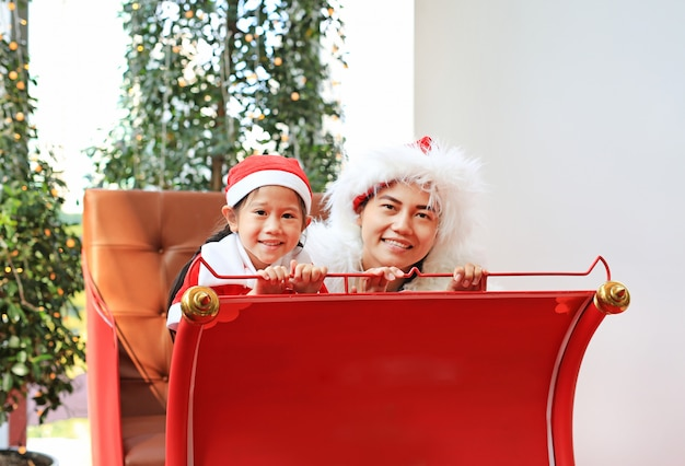 Glückliches kleines kindermädchen und ihre mutter in sankt-kostüm auf rotem schlitten. fröhliche weihnachten.