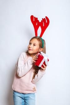 Glückliches kleines lächelndes mädchen mit weihnachtsgeschenkbox. weihnachtskonzept.