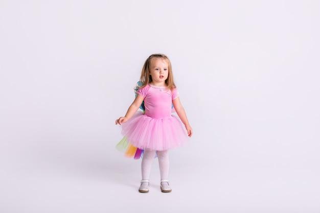 Glückliches kleines lustiges emotionales kindermädchen im niedlichen rosa ponykostüm der weihnacht