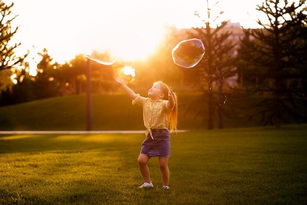 Glückliches kleines mädchen 4-5 jahre alt spielt mit seifenblasen im sommer im park. lebensstil der kinder.