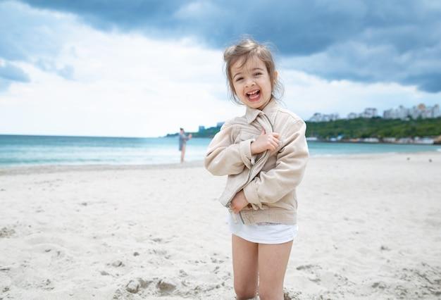 Glückliches kleines mädchen an einem sonnigen tag am strand am meer.