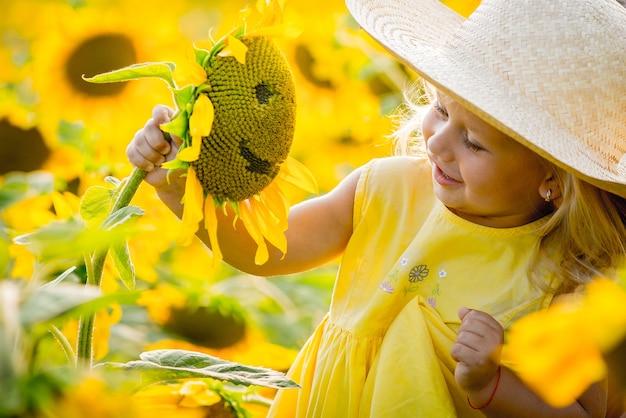 Glückliches kleines mädchen auf dem feld der sonnenblumen im sommer. schönes kleines mädchen in sonnenblumen