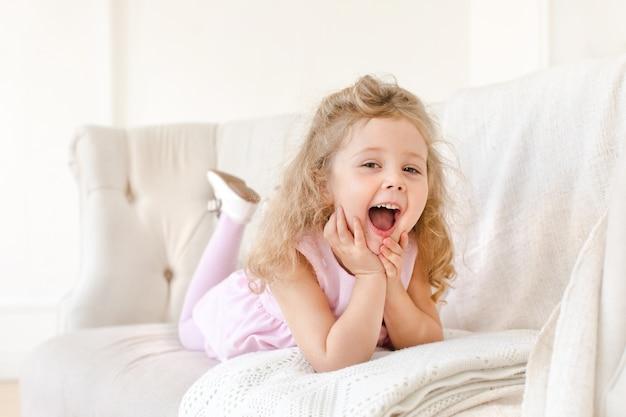 Glückliches kleines mädchen auf weißem sofa