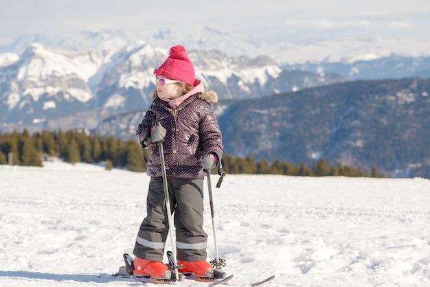 Glückliches kleines mädchen, das abwärts ski fährt