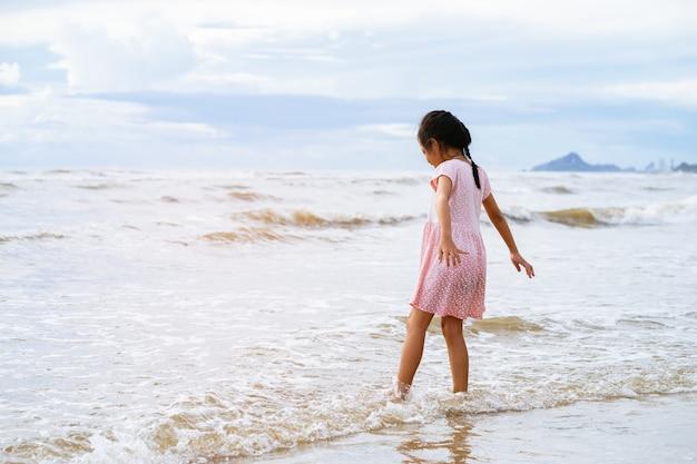 Glückliches kleines mädchen, das am strand spielt