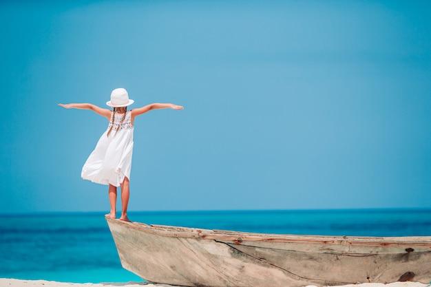 Glückliches kleines mädchen, das am strand während des karibikurlaubs geht