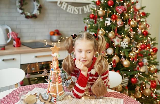 Glückliches kleines mädchen, das am tisch in der häuslichen küche mit weihnachtsbaum sitzt