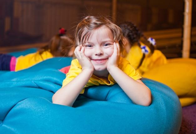 Glückliches kleines mädchen, das auf der stuhl-tasche im kinderunterhaltungszentrum ruht