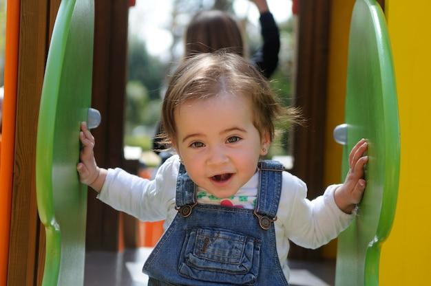 Glückliches kleines mädchen, das auf einem städtischen spielplatz spielt.