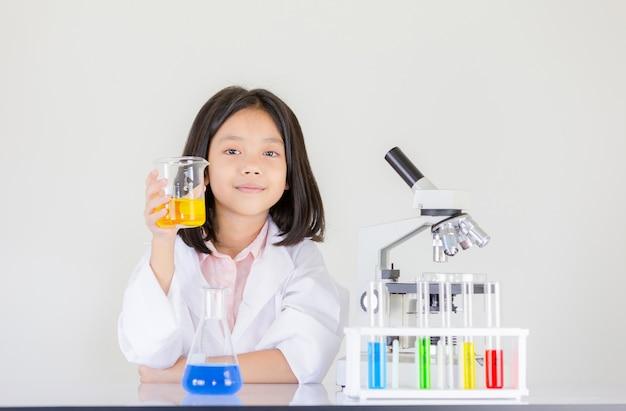 Glückliches kleines mädchen, das chemische experimente am labor tuend spielt