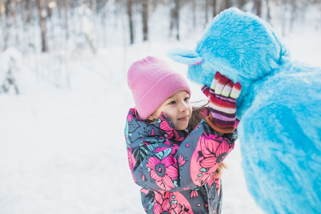 Glückliches kleines mädchen, das die wangen einer frau in einem flauschigen blauen kostüm kneift