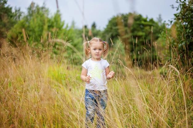 Glückliches kleines mädchen, das draußen lächelt. schönes junges mädchen, das auf sommerfeld ruht