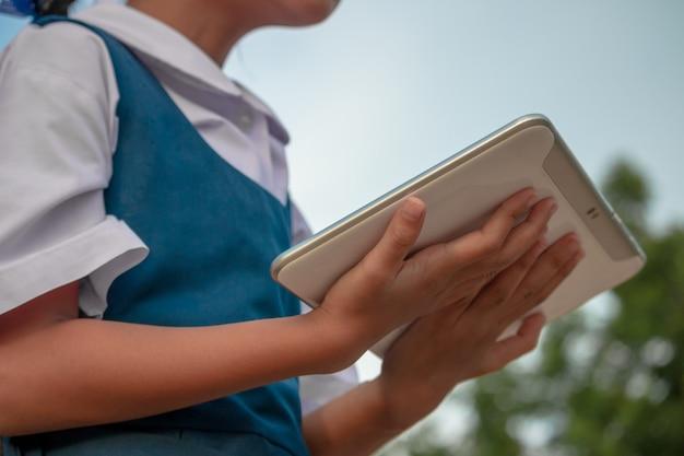 Glückliches kleines mädchen, das draußen tablet-pc im sommerpark hält