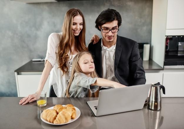 Glückliches kleines mädchen, das einen film am computer mit ihrem vater und ihrer mutter zu hause sieht Premium Fotos