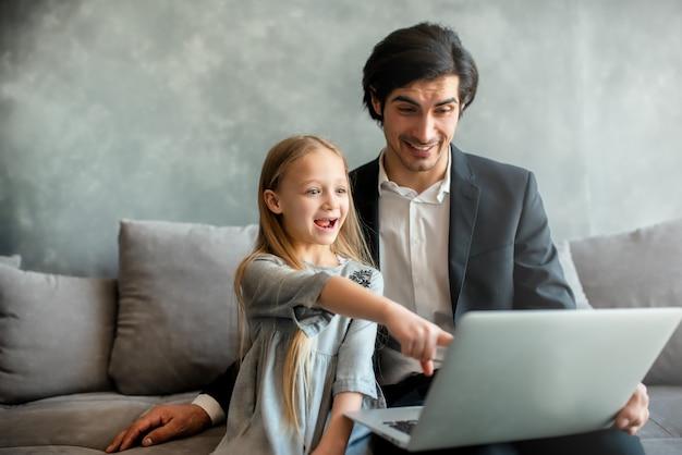 Glückliches kleines mädchen, das einen film am computer mit ihrem vater zu hause sieht