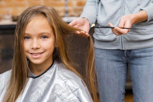 Glückliches kleines mädchen, das einen haarschnitt bekommt