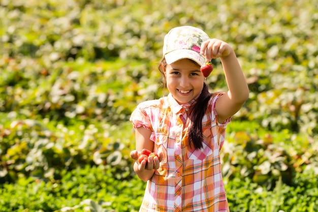 Glückliches kleines mädchen, das erdbeeren auf einer plantage pflückt und isst
