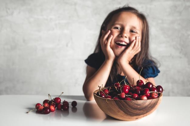 Glückliches kleines mädchen, das frische kirsche auf teller isst. frische reife kirschen. süßkirschen. mädchen, das süßes kirsch-bio-öko-produkt, bauernhof isst. kein gvo