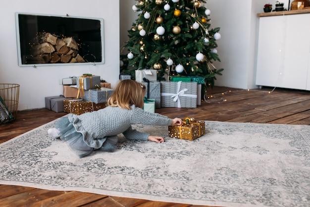 Glückliches kleines mädchen, das geschenkbox, weihnachtsbaum hält. frohe weihnachten und schöne feiertage!