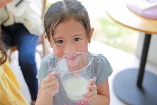 Glückliches kleines mädchen, das glas frische milch von den kühen in der molkerei hält.