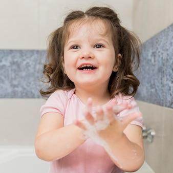 Glückliches kleines mädchen, das hände wäscht