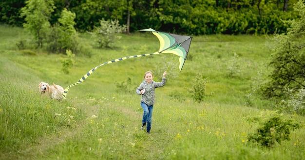 Glückliches kleines mädchen, das hellen drachen draußen auf natur im frühjahr fliegt