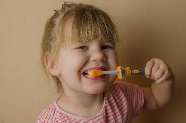 Glückliches kleines mädchen, das ihre zähne putzt. platz kopieren