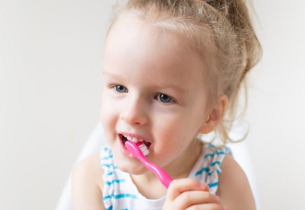 Glückliches kleines mädchen, das ihre zähne, rosa zahnbürste, zahnpflege, morgen-nachtgesunder konzept-lebensstil putzt