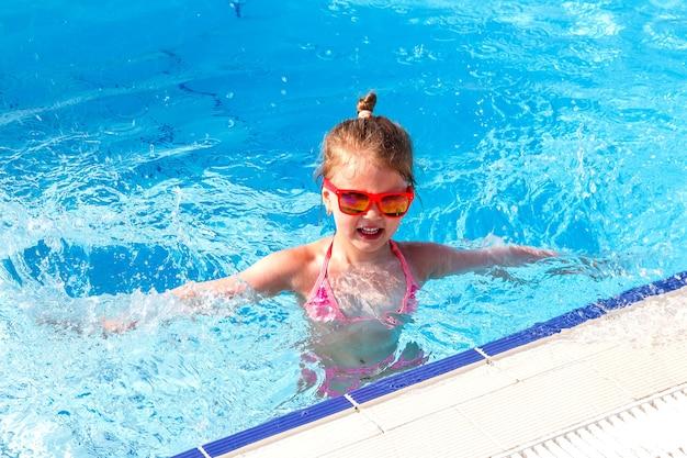 Glückliches kleines mädchen, das im sommer im urlaub im pool schwimmt