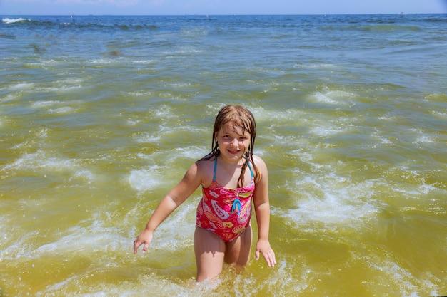Glückliches kleines mädchen, das im wasser schwimmt