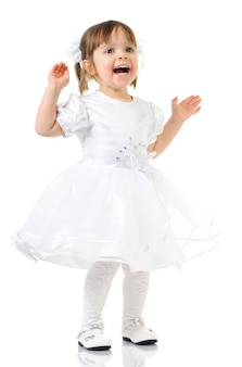 Glückliches kleines mädchen, das im weißen kleid und in den schuhen lächelt und aufwirft, hände auseinander gespreizt, heller hintergrund für ein foto in voller länge