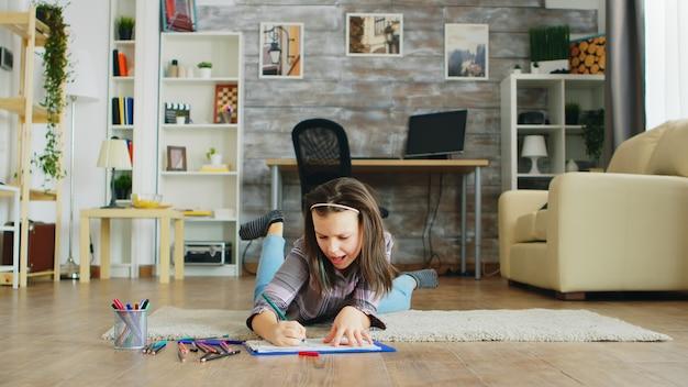 Glückliches kleines mädchen, das in der wohnzimmerzeichnung auf dem boden liegt. intelligentes kind.