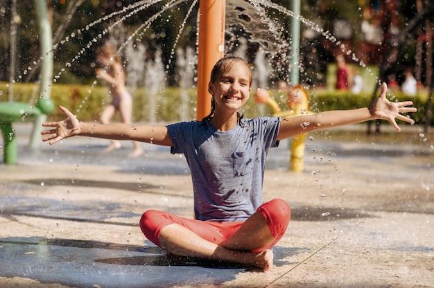 Glückliches kleines mädchen, das in der yoga-pose auf wasserspielplatz im sommerpark sitzt. kinderfreuden im aquapark