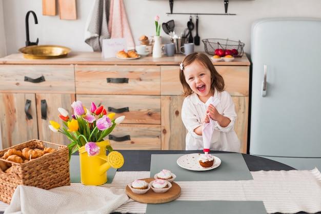 Glückliches kleines mädchen, das kleinen kuchen macht