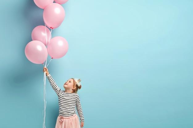 Glückliches kleines mädchen, das luftballons hält