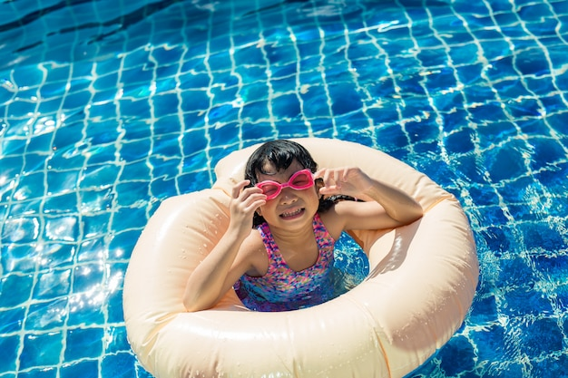 Glückliches kleines mädchen, das mit buntem aufblasbarem ring swimmingpool im im freien am heißen sommertag sich entspannt