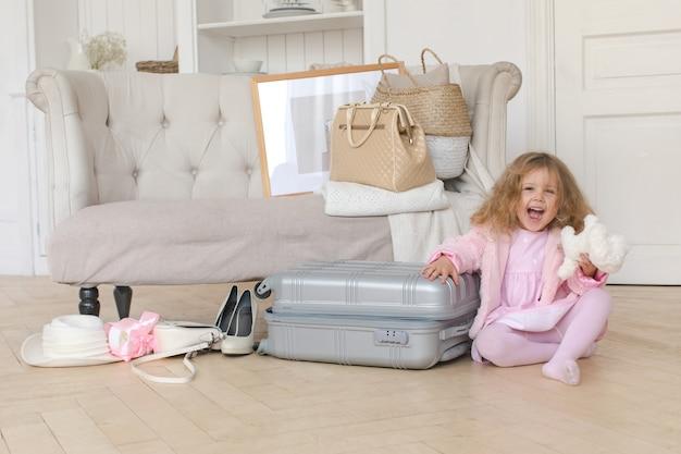 Glückliches kleines mädchen, das mit einem retro- koffer spielt