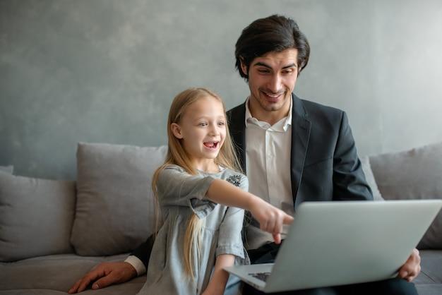 Glückliches kleines mädchen, das mit ihrem vater einen film auf dem computer sieht