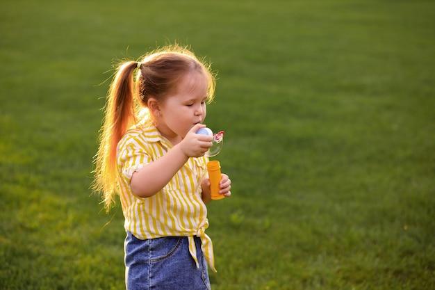 Glückliches kleines mädchen, das mit seifenblasen im park spielt