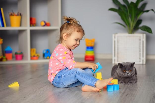 Glückliches kleines mädchen, das mit spielzeug zu hause, im kindergarten oder im kindergarten spielt. entwicklung des kindes.