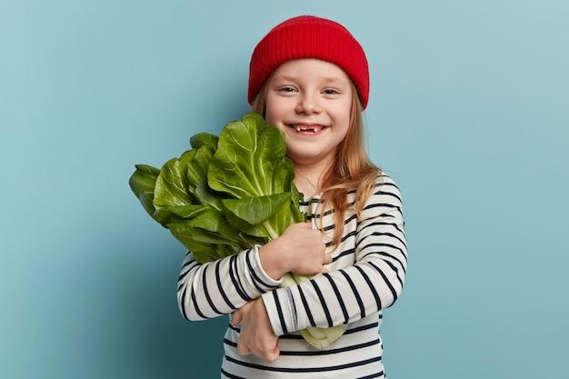 Glückliches kleines mädchen, das salat hält