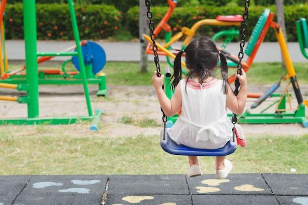 Glückliches kleines mädchen, das schwingen am spielplatz spielt. glücklich, familie, schwester concept.