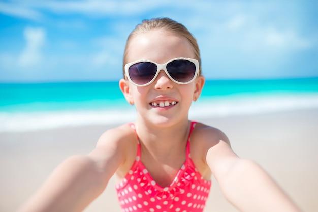 Glückliches kleines mädchen, das selfie am tropischen strand auf exotischer insel nimmt