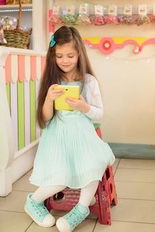 Glückliches kleines mädchen, das tablet-computer im süßwarenladen benutzt