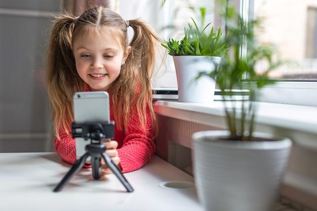 Glückliches kleines mädchen, das telefon benutzt, auf dem bildschirm lächelt, zu hause online kommuniziert, per videoanruf spricht, filme oder online-unterricht ansieht. konzept der generation z