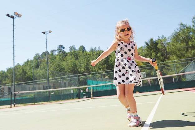 Glückliches kleines mädchen, das tennis spielt. sommersport