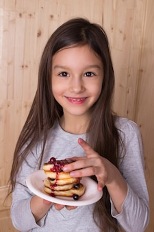 Glückliches kleines mädchen, das traditionelle russische pfannkuchen mit beerenmarmelade isst. maslenitsa-konzept