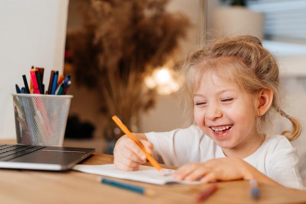 Glückliches kleines mädchen, das über ihren laptop lacht und hausaufgaben in einem notizbuch, hauptlernkonzept macht