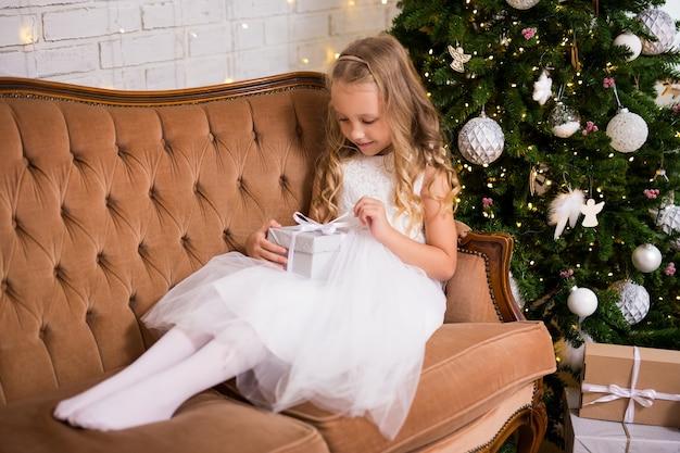 Glückliches kleines mädchen, das weihnachtsgeschenk im wohnzimmer mit verziertem weihnachtsbaum öffnet